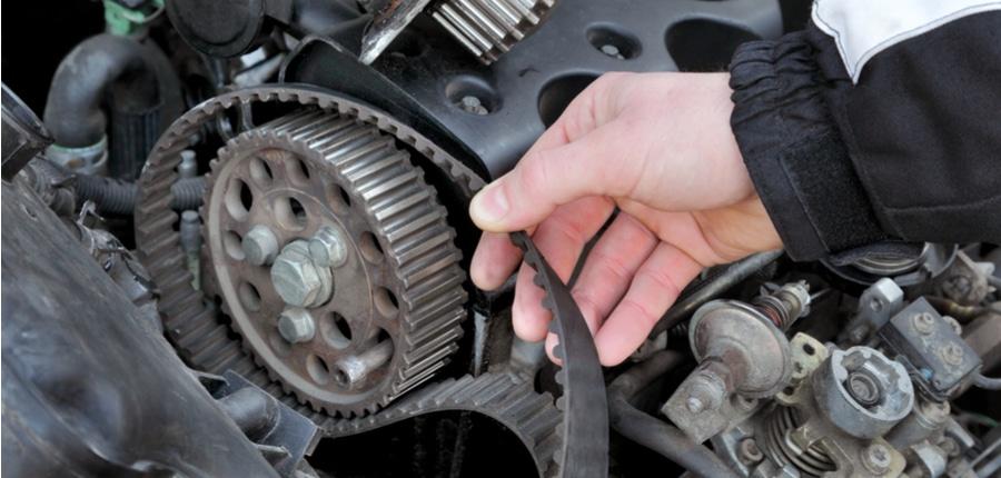 mechanic replacing timing belt at camshaft