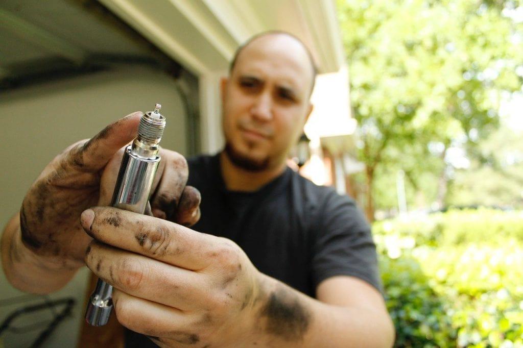 spark plug in a dirty hand